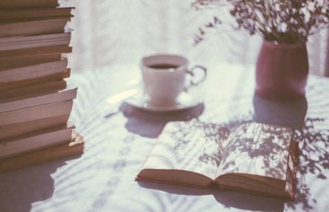 A table with an open book, pile of books, mug and pot of flowers.
